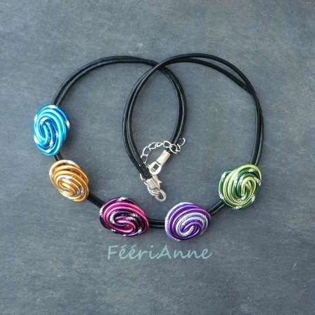 Collier fantaisie composé de cinq cabochons turquoise, or, rose, lilas et vert montés sur deux brins de cuir noir