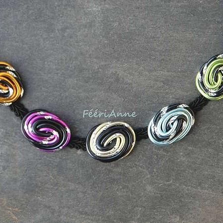 Collier fantaisie composé de cinq cabochons de fil alu noir et vert, bleu, perle, lavande ou or montés sur passementerie noire