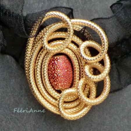 Médaillon fantaisie rétro en fil aluminium doré et perle métallisée orange monté sur un ruban élastique à frou-frous en organza noir