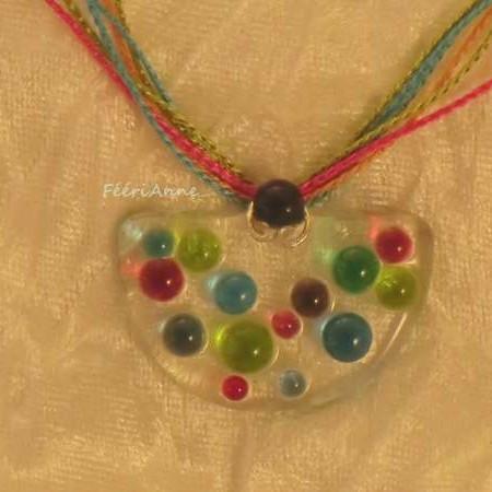 Pendentif demie lune en verre fusing transparent agrémenté de demie sphères de verre coloré turquoise, vert, rouge et gris monté sur fils soyeux turquoise, vert rose et orange