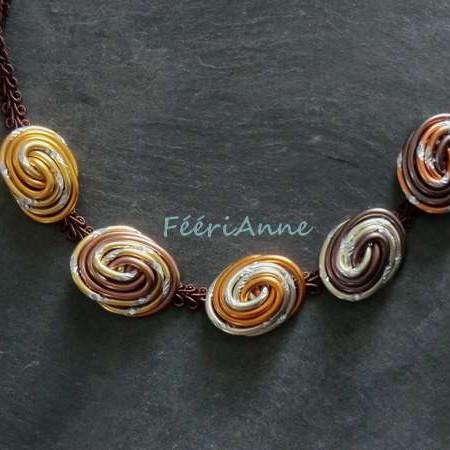 Ras de cou fantaisie composé de cinq cabochons en fil alu dans un camaieu de brun montés sur un cordon de passementerie chocolat