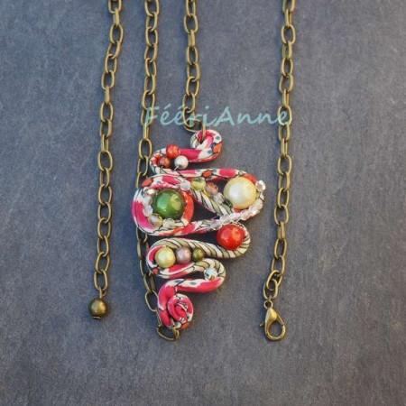 Bijou de cheveux en liberty rose et vert pâle agrémenté de perles magiques vertes, jaunes et orange et monté sur une chaine couleur bronze