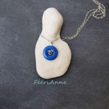 Donut en lapis lazuli monté en pendentif grâce à une attache centrale artisanale modelée à la main en bronze blanc représentant un petit bouquet de trois roses