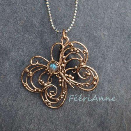 Papillon finement modelé en bronze doré agrémenté d'un petit cabochon de labradorite aux doux reflets bleus