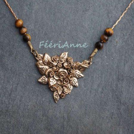 Pendentif artisanal triangulaire représentant une gerbe de roses, monté sur une chaîne serpentine bronze ornée de perles d'œil de tigre