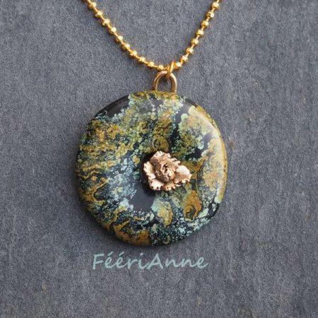 Joli donut de turquoise vert d'eau, ocre et noire montée sur une bélière représentant une pivoine modelée à la main en bronze doré