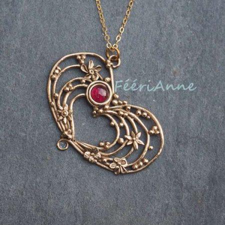 Cœur pendentif artisanal en dentelle de bronze doré agrémenté de minuscules fleurs et billes de bronze et orné d'un lumineux rubis de synthèse rose foncé