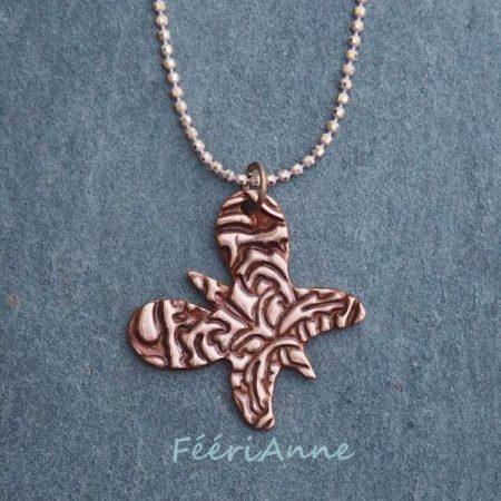 Petit pendentif papillon artisanal en cuivre émaillé avec une peinture-émail brique et monté sur une chaîne boule à facettes métal argenté et beige rosé