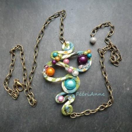 Bijou de cheveux fantaisie revêtu de liberty tons pastel bleu, vert et blanc agrémenté de perles magiques multicolores