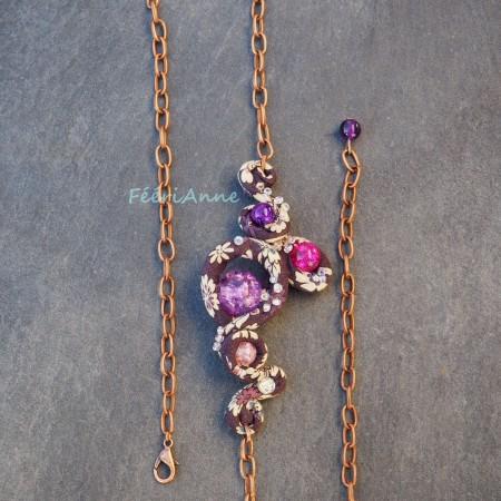 Bijou de cheveux revêtu de liberty violet à fleurs blanches, agrémenté de perles de verre craquelé en dégradé de violet à rose et monté sur une chaine couleur cuivre