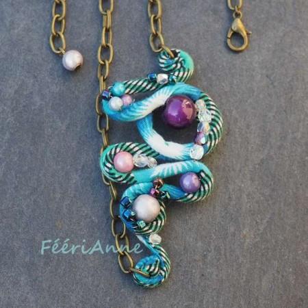 Bijou de cheveux fantaisie turquoise agrémenté de perles magiques en camaïeu de violet et rose, monté sur une chaine couleur bronze