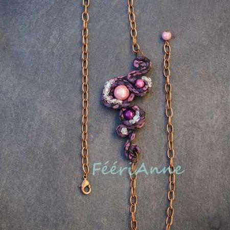 Bijou de cheveux recouvert de liberty violet agrémenté de perles magiques roses assorties et de perles de verre facettées cristal, monté sur une chaine couleur cuivre
