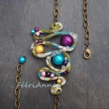 Bijou de cheveux fantaisie recouvert de liberty pastel vert, bleu et blanc, perlé à la main de perles multicolores et monté sur une chaîne bronze